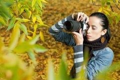 Fotógrafo hermoso de la muchacha en la naturaleza (en follaje) Imagen de archivo