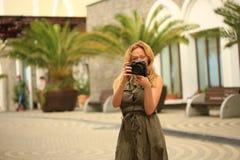 Fotógrafo hermoso de la mujer que hace las fotos en un parque de atracciones Un blogger feliz hace una imagen divertida para su b Imagenes de archivo