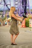 Fotógrafo hermoso de la mujer que se toma con una cámara en un parque de atracciones Un blogger feliz hace una imagen divertida Fotos de archivo libres de regalías