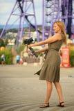 Fotógrafo hermoso de la mujer que se toma con una cámara en un parque de atracciones Un blogger feliz hace una imagen divertida Foto de archivo libre de regalías