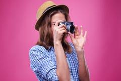 Fotógrafo joven atractivo que enfoca mientras que usa la cámara retra Imágenes de archivo libres de regalías