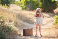 Fotógrafo joven con la cámara vieja en una carretera nacional Foto de archivo libre de regalías