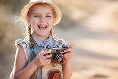 Fotógrafo joven con la cámara vieja en una carretera nacional Fotografía de archivo
