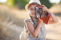 Fotógrafo joven con la cámara vieja en una carretera nacional Fotos de archivo