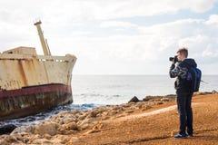 Fotógrafo joven en la playa Fotógrafo del viajero con la cámara digital Imagen de archivo