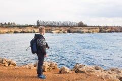Fotógrafo joven en la playa Fotógrafo del viajero con la cámara digital Foto de archivo libre de regalías