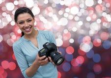 fotógrafo joven feliz con la cámara en las manos Fondo rosado, azul y blanco del bokeh Imágenes de archivo libres de regalías