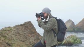 Fotógrafo joven que toma las fotos del acantilado del océano con la cámara de DSLR metrajes