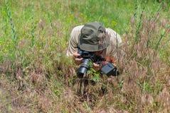 Fotógrafo maduro que toma una foto macra Imágenes de archivo libres de regalías