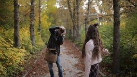 Fotógrafo masculino no parque do outono que toma imagens do adolescente da menina filme