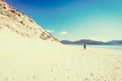 Fotógrafo masculino novo com dreadlocks em uma praia branca ensolarada com as dunas de areia altas, Luskentyre da areia, ilha de  Fotos de Stock