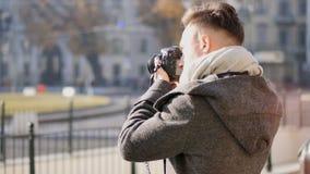 Fotógrafo masculino novo considerável que toma a fotografia exterior video estoque