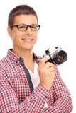 Fotógrafo masculino novo que guarda uma câmera Imagem de Stock Royalty Free
