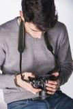 Fotógrafo masculino novo que olha fotografias em seu photocamera Imagem de Stock Royalty Free