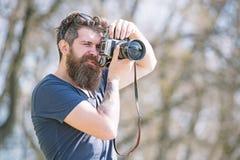 Fotógrafo masculino novo que toma imagens no parque com câmera do vintage, passatempo e conceito da atividade de lazer bearded foto de stock