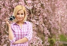 Fotógrafo Muchacha rubia con la cámara retra sobre Cherry Blossom Fotografía de archivo