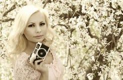 Fotógrafo. Mujer rubia con la cámara retra sobre Cherry Blossom Imagen de archivo libre de regalías