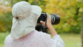 Fotógrafo-naturalista asiático en un sombrero grande de la quemadura Fotografía los animales, los soportes de la cámara en un trí almacen de video