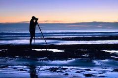 Fotógrafo no mar no crepúsculo Imagens de Stock Royalty Free