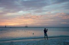 Fotógrafo no por do sol com os barcos de vela ancorados Fotos de Stock Royalty Free
