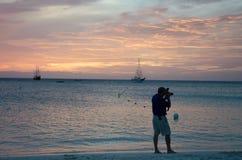 Fotógrafo no por do sol com os barcos de vela ancorados Fotos de Stock
