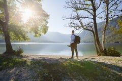 Fotógrafo novo que olha o lago, em um dia ensolarado bonito imagens de stock