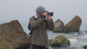 Fotógrafo Outdoorsy con una barba que captura un mar tempestuoso almacen de video