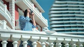 Fotógrafo profesional de la mujer en las gafas de sol y el vestido rayado que toman la foto usando cámara del vintage almacen de video