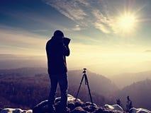 Fotógrafo profesional de la naturaleza en el acantilado nevoso Imagen de archivo libre de regalías
