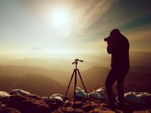 Fotógrafo profesional de la naturaleza en el acantilado nevoso Imágenes de archivo libres de regalías