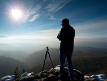 Fotógrafo profesional de la naturaleza en el acantilado nevoso Foto de archivo