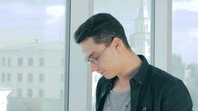Fotógrafo profesional que toma imágenes con la cámara profesional cerca de ventana panorámica en oficina moderna metrajes