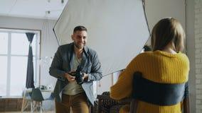 Fotógrafo profesional que toma las fotos del modelo en la cámara digital que trabaja en estudio de la foto fotografía de archivo libre de regalías