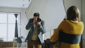 Fotógrafo profesional que toma las fotos del modelo en la cámara digital que trabaja en estudio de la foto fotos de archivo