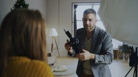 Fotógrafo profesional que toma las fotos del modelo en la cámara digital que trabaja en estudio de la foto foto de archivo