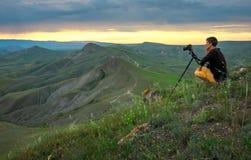 Fotógrafo profesional que usa un trípode, tomando una foto de un paisaje de la montaña foto de archivo