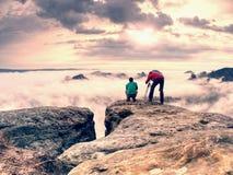 Fotógrafo profissional em joelhos no tripé que olha na paisagem da queda imagem de stock