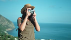 Fotógrafo profissional fêmea que toma a imagem usando a câmera do filme do vintage no pico da montanha video estoque