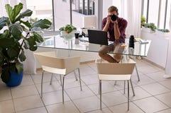 Fotógrafo profissional que senta-se em seu estúdio home Imagem de Stock