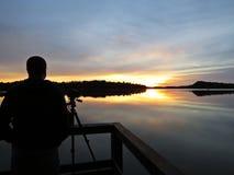 Fotógrafo profissional Silhouette com o tripé durante o por do sol sobre o lago bonito com o céu nebuloso no fundo imagem de stock