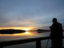 Fotógrafo profissional Silhouette com o tripé durante o por do sol sobre o lago bonito com o céu nebuloso no fundo foto de stock