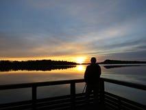 Fotógrafo profissional Silhouette com o tripé durante o por do sol sobre o lago bonito com o céu nebuloso no fundo foto de stock royalty free