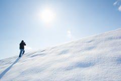 Fotógrafo que captura imagen en la nieve Foto de archivo libre de regalías