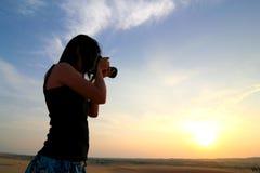 Fotógrafo que fotografa no nascer do sol Fotografia de Stock Royalty Free