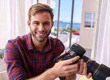 Fotógrafo que guarda a câmera e o sorriso Fotografia de Stock Royalty Free