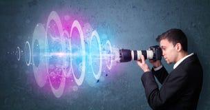 Fotógrafo que hace las fotos con el haz luminoso potente Imagen de archivo