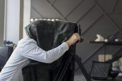 Fotógrafo que oculta debajo de un cabo negro con la cámara retra imagenes de archivo