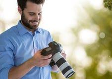 fotógrafo que olha as imagens na câmera Verde e branco borrou luzes e alarga-se fundo Imagem de Stock