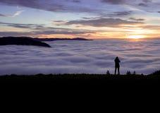 Fotógrafo que se coloca sobre la niebla en la colina Imagenes de archivo