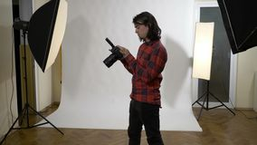 Fotógrafo que se sienta en su estudio de la foto que comprueba las fotografías de su cámara digital y que son satisfechas de su t almacen de metraje de vídeo